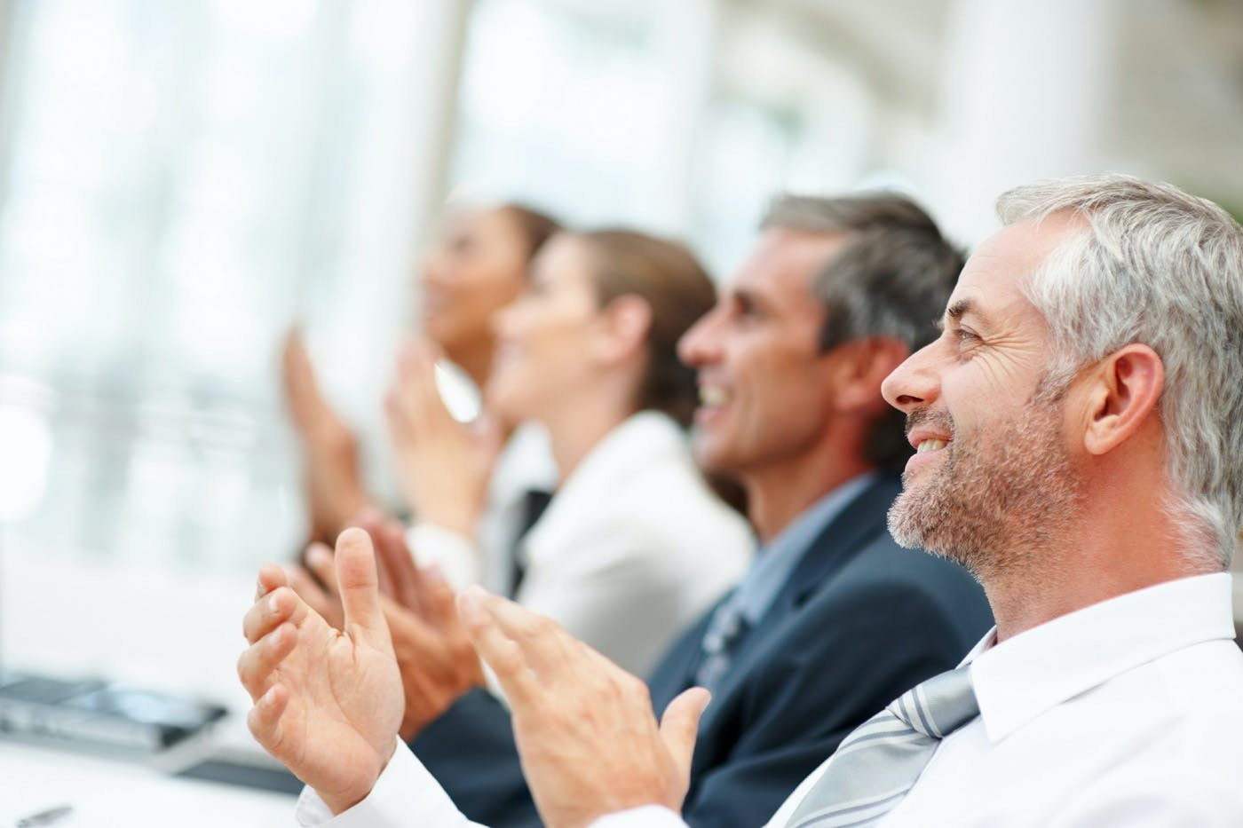 Group of happy business people clapping their hands