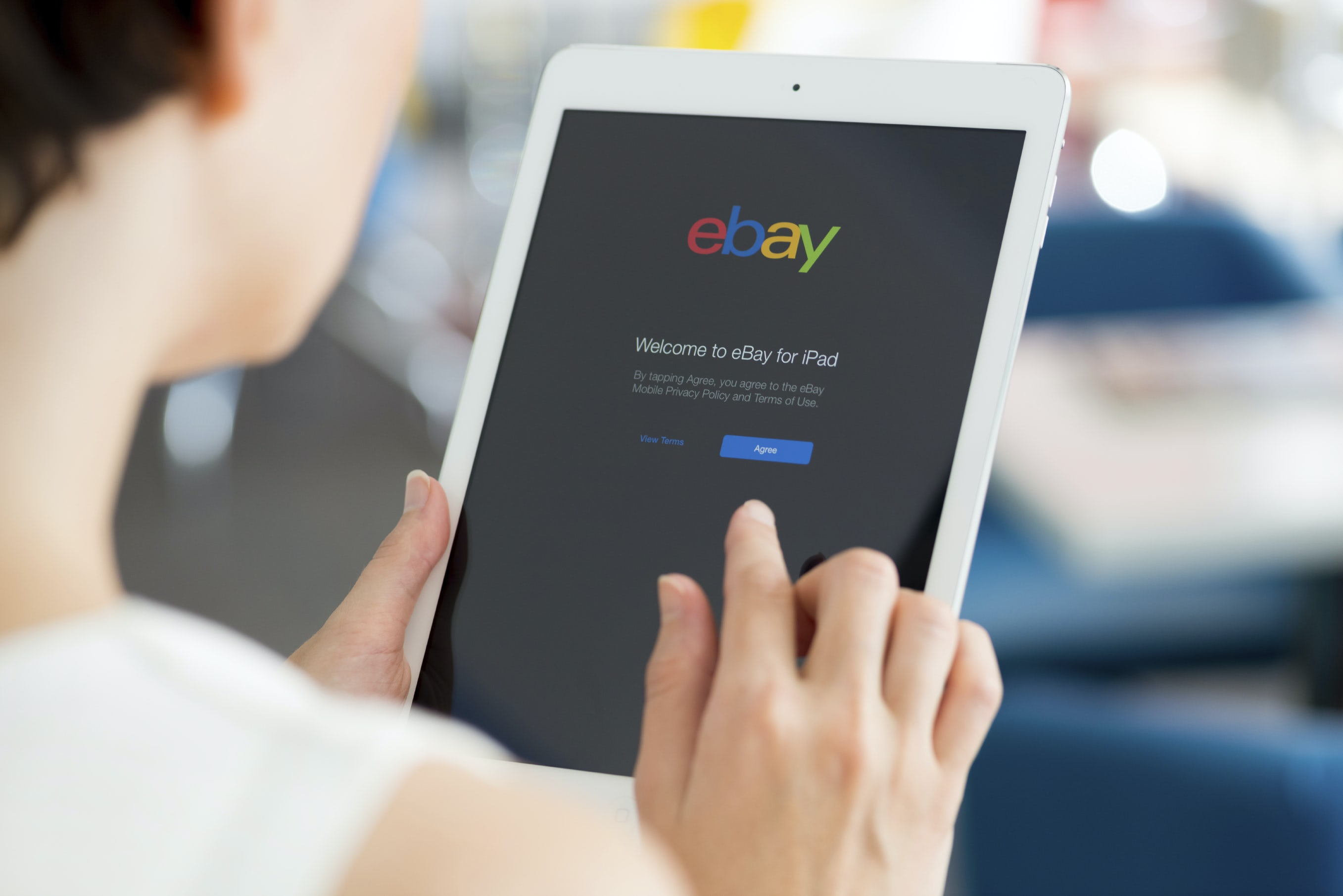 KIEV, UKRAINE - MAY 21, 2014: Woman holding a white Apple iPad Air with eBay welcome message on a screen. eBay is the worldwide online auction and shopping website that founded in September 3, 1995.