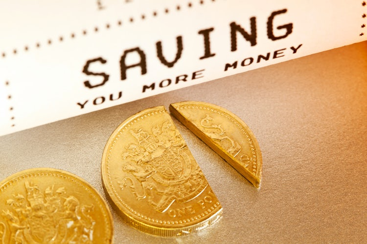 """Saving you more money. Whether by discounting a percentage of the cost, or handing back a cashback, the concept of Saving you money is illustrated with a checkout till receipt and a cut one pound sterling coin."""