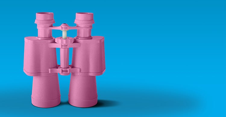 Pink binoculars on blue background